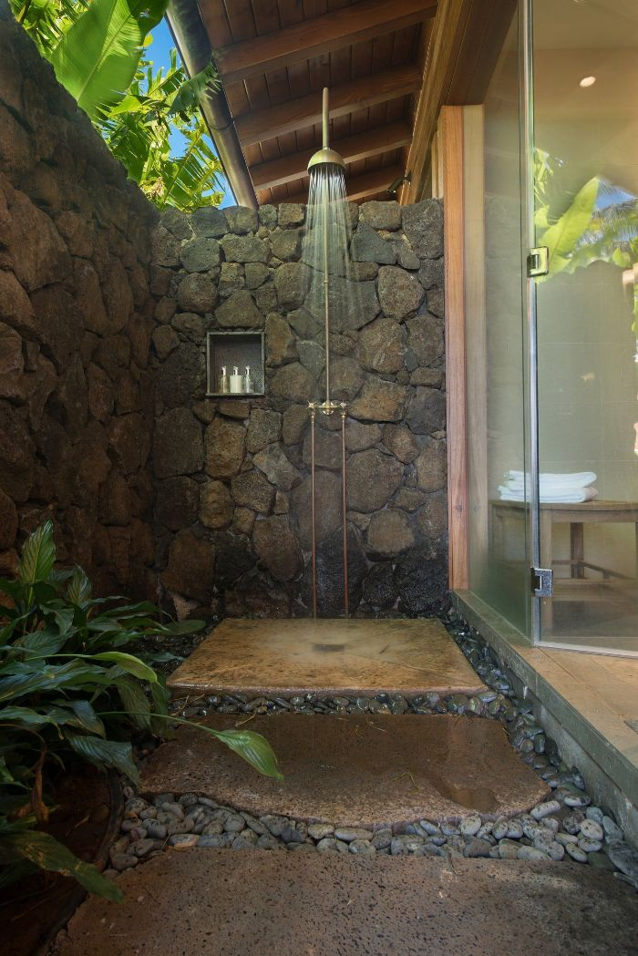 hawaiian style outdoor shower enclosure made of rocks stone tiles and rocks on the floor