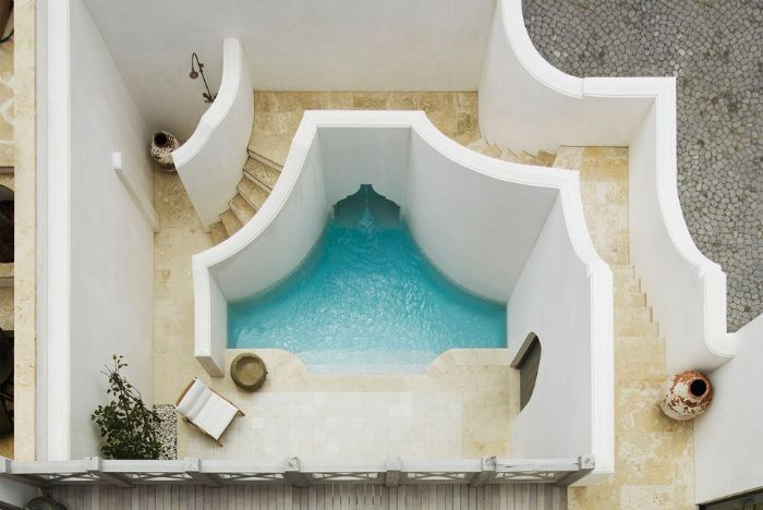 moroccan style pool with lounge chair outside showers white walls tiled floor