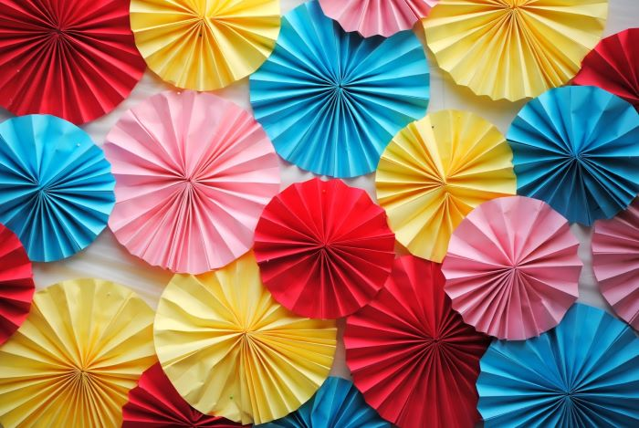 baby shower centerpiece ideas close up photo of blue red yellow pink fans arranged together for backdrop