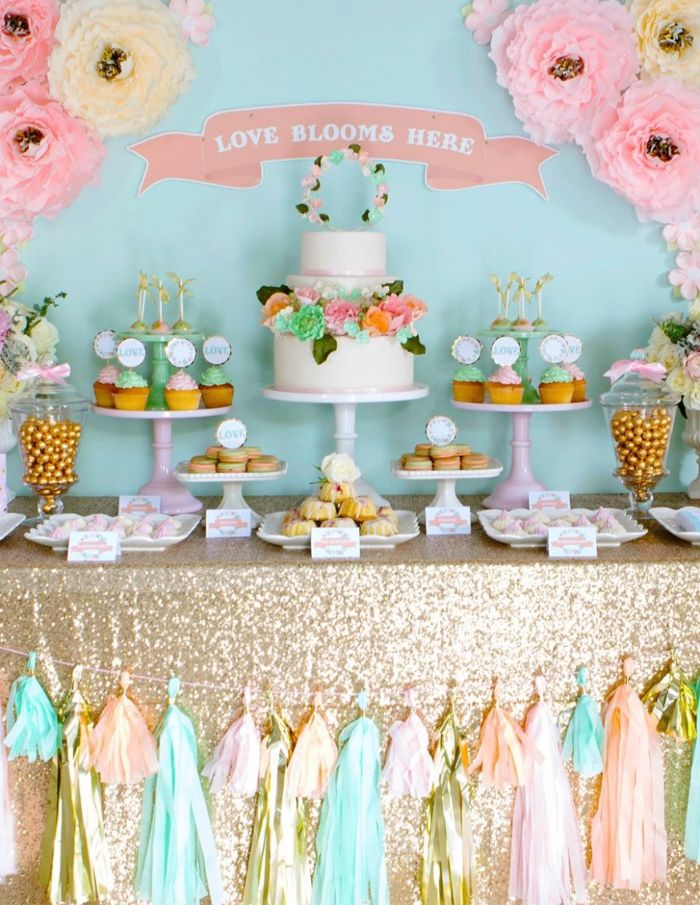 baby shower decorations dessert table with cake stands with cupcakes white cake with flowers paper flowers on the wall