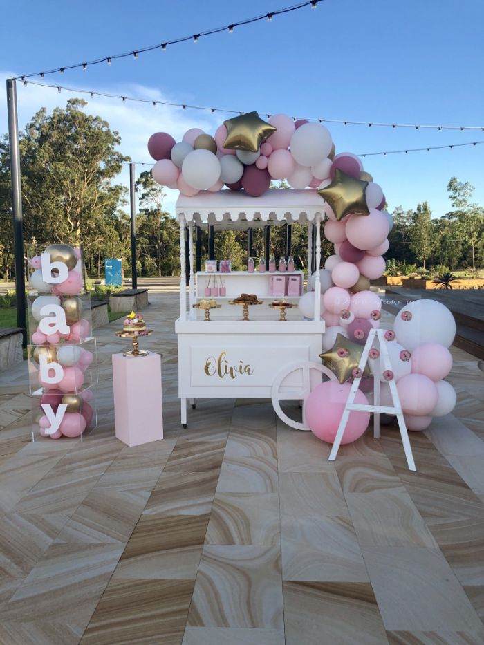baby shower ideas for girls food cart with desserts decorated with pink purple gold balloons baby blocks on the side filled with balloons