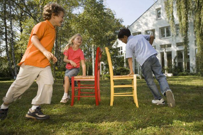 backyard games for kids three kids running around two chairs playing musical chairs