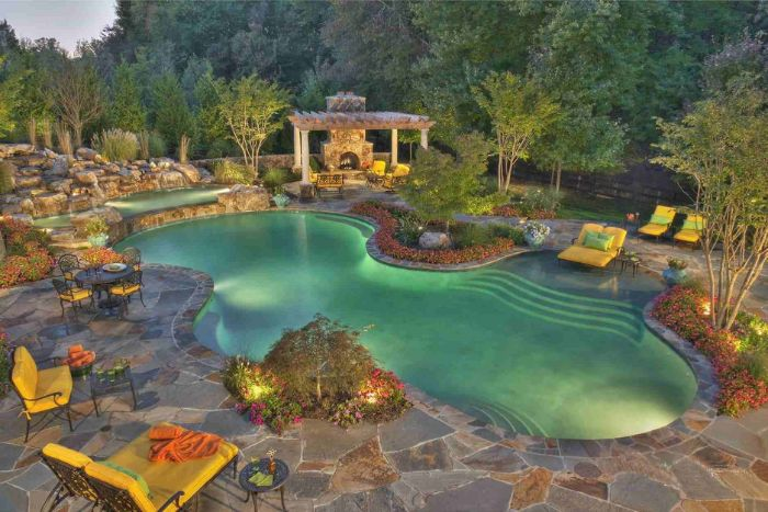 backyard pool ideas free flow pool with lights surrounded by rocks and garden furniture