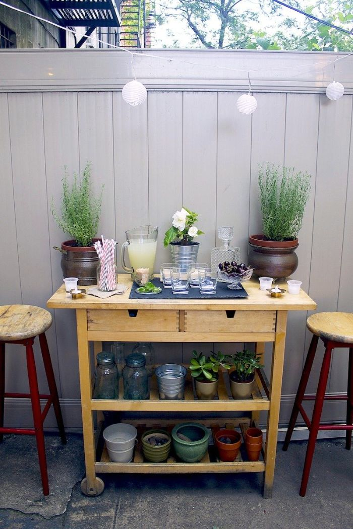 bar stools next to small cart with two shelves filled with potted plants outdoor patio bar mimosa ingredients glasses on top
