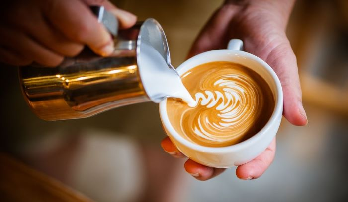 barista pouring milk foam into coffee cup creating decoration how to make coffee