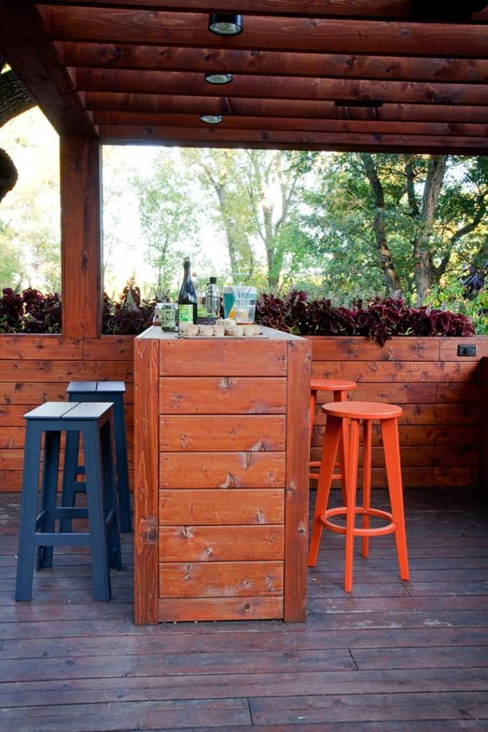 black and orange bar stools next to outdoor wooden bar inside wooden enclosure