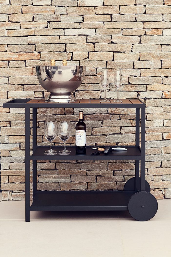 black cart with wine glasses wine bottles on the shelves outside bar ideas in front of stone wall