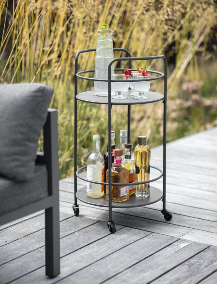 black metal trolley with different bottles and glasses on it outdoor wooden bar