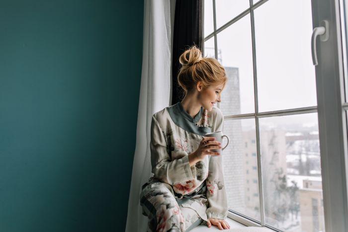 blonde woman sitting on window frame window installation drinking coffee turquoise wall