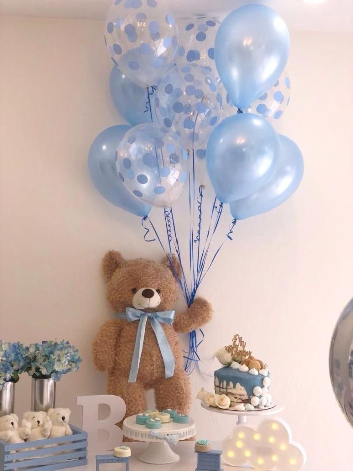 blue balloons held by teddy bear baby shower ideas for girls placed on dessert table with cake blue and white flower bouquets
