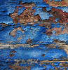blue paint in pieces coming off of wooden surface lead poisoning close up photo