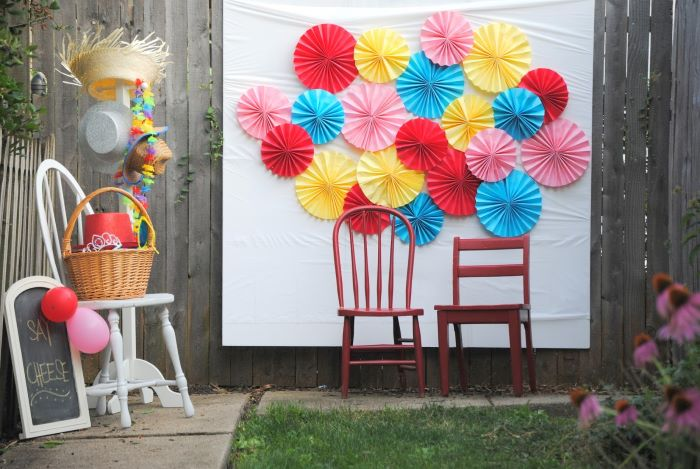 blue red pink yellow paper fans arranged on white surface baby shower decoration ideas for boy two chairs in front of it photo backdrop