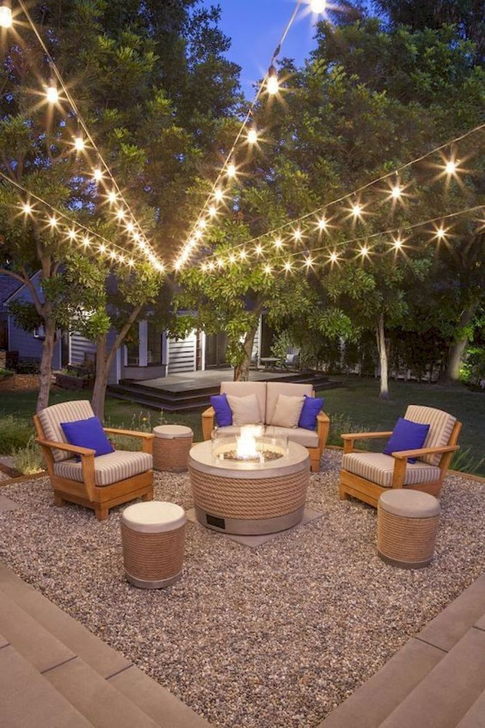 blue throw pillows on garden furniture backyard string lights hanging above from the trees