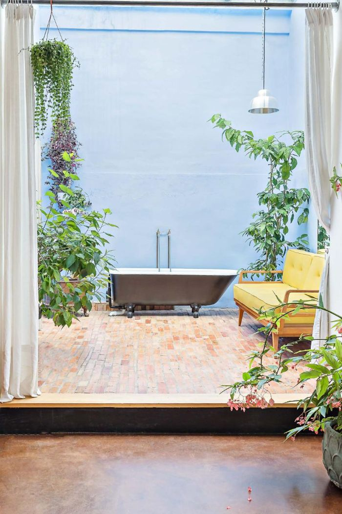 blue wall diy outdoor shower bathtub and sofa surrounded by plants and flowers