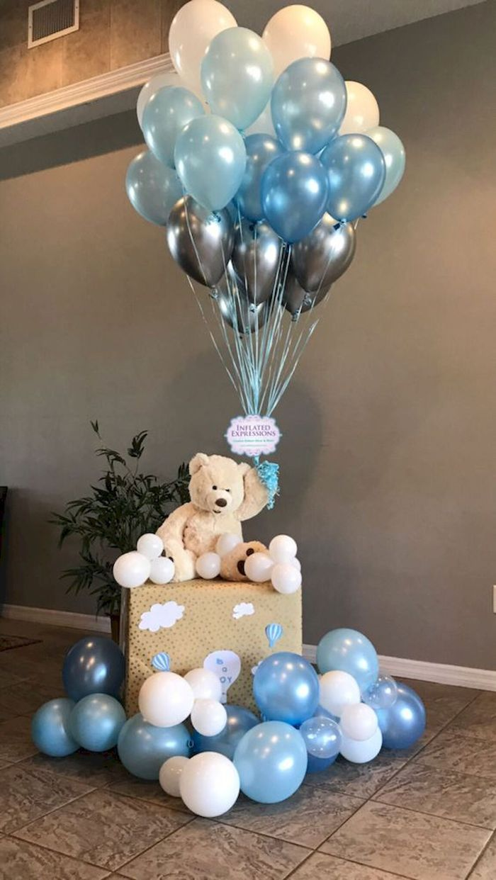 blue white gray balloons being held by teddy bear sitting on a large box baby shower decorations
