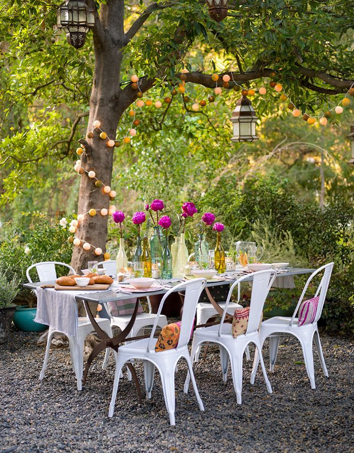 bouquets of flowers in the middle of dining table placed under a tree backyard string lights string of small lanterns wrapped around the tree