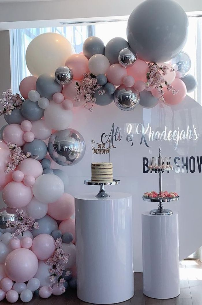 boy baby shower decorations arch made with gray silver pink white baloons cake and cake stand with cupcakes