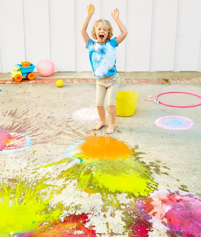 boy smiling playing with paint outdoor games for kids yellow and pink paint splattered on the concrete