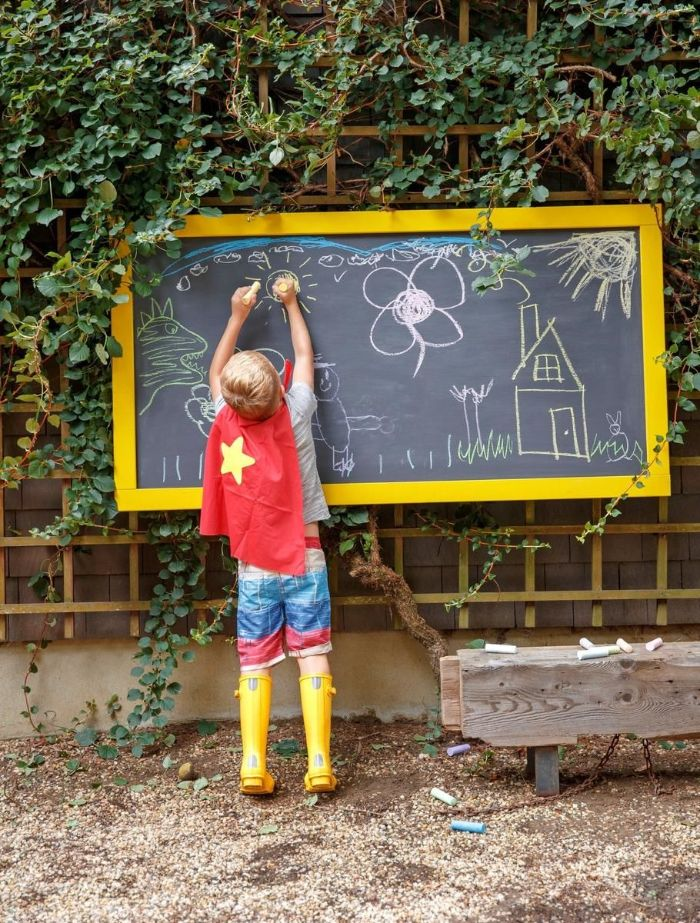 boy wearing superhero cape yellow boots drawing on a chalk board games to play outside