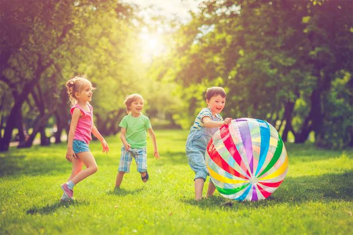 boys and girl playing on a field surrounded by trees outdoor fun for kids playing with large plastic ball