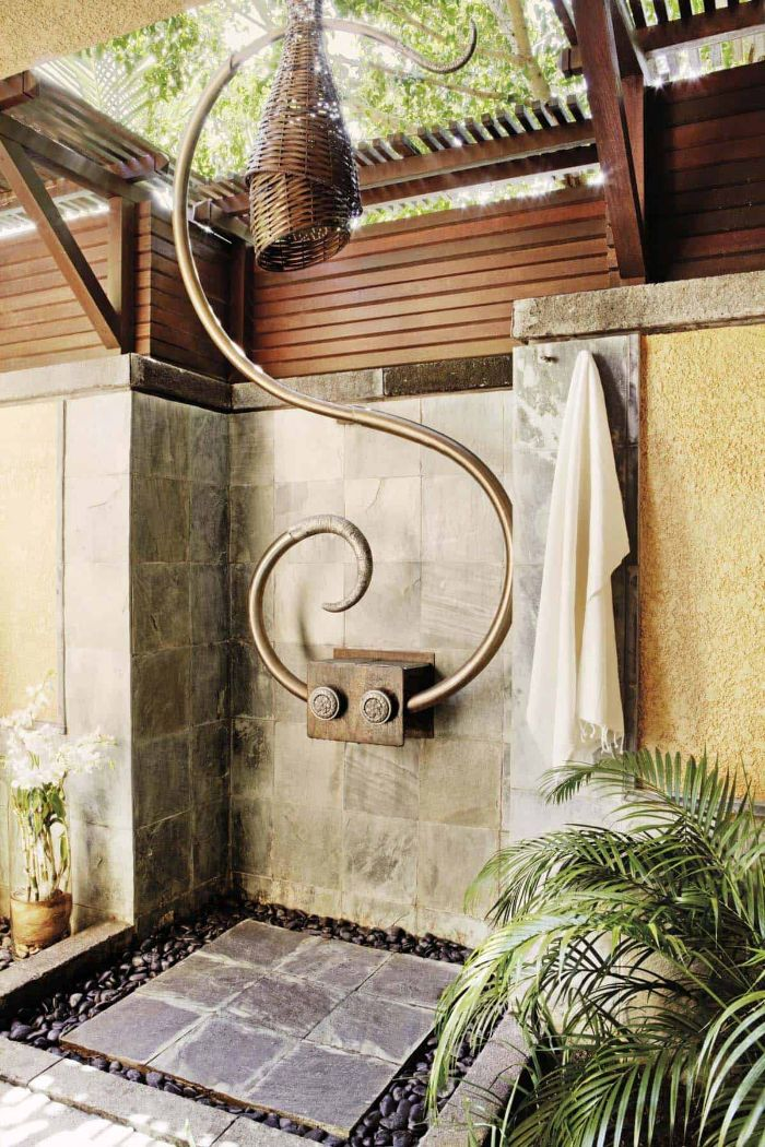 brass and rattan shower head wood outdoor shower stone tiles on the walls and floor surrounded by small rocks