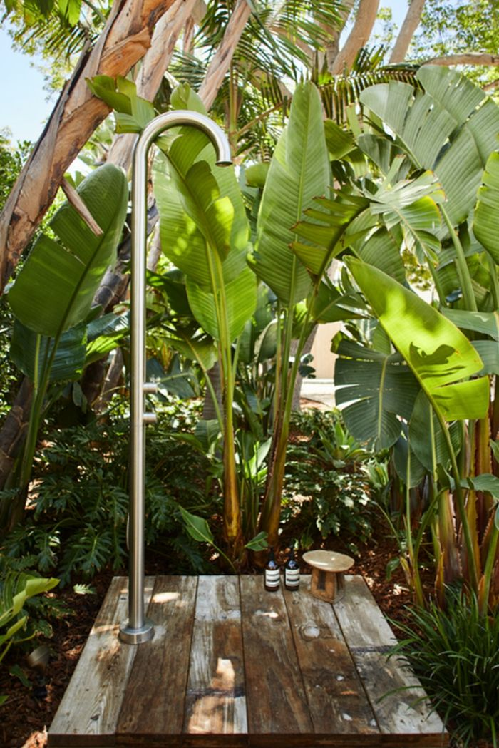 brass metal tube wood floor diy outdoor shower enclosure minimalistic design surrounded by palm trees