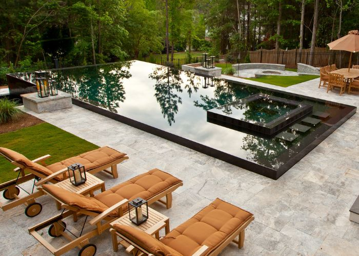 brown cushions on lounge chairs next to large pool backyard swimming pool surrounded by tall trees