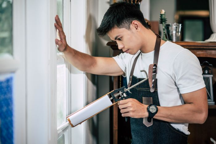 carpenter wearing white t shirt holds glue door installation attaches window with white frames