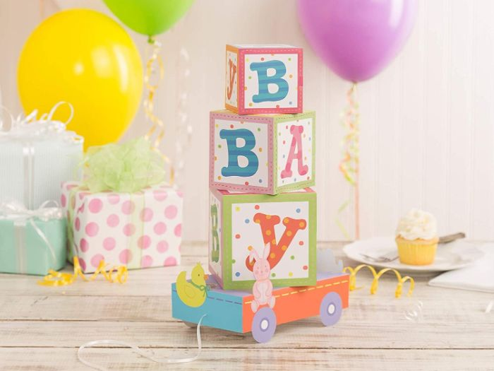 carton centerpiece with baby blocks spelling baby baby shower decorations girl balloons in the background