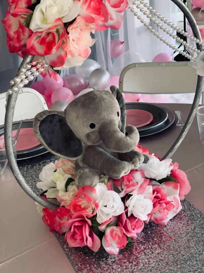 centerpiece made with faux roses velvet toy elephant baby shower decorations placed on silver glitter table runner