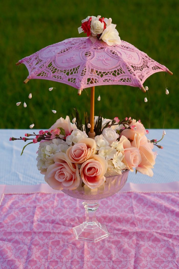 centerpiece made with roses boy baby shower decorations small pink umbrella over it placed on pink table runner