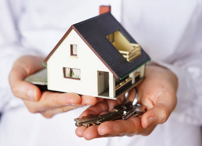 close up photo of hands holding a set of keys house in spain house model