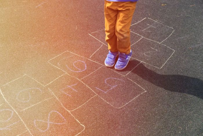 close up photo of kid wearing orange pants blue sneakers playing hop scotch outdoor activities for toddlers