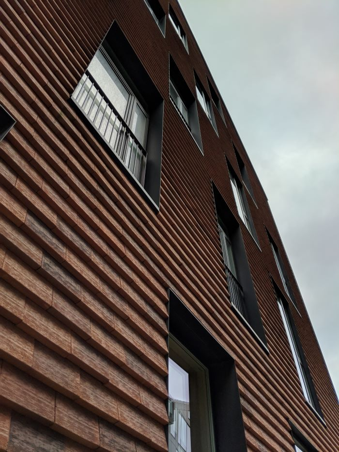 close up photo of tall apartment building with wood siding lots of windows home siding
