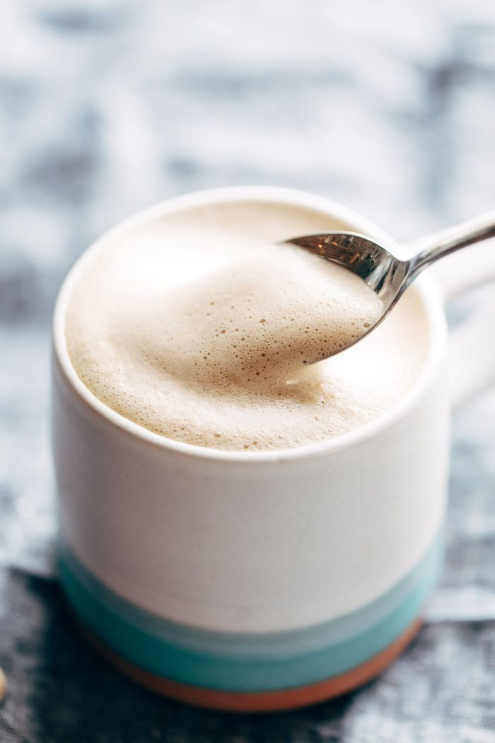 coffee to water ratio cashew latte with foam on top poured in ceramic mug