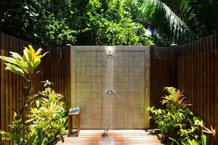 colorful tiles on the wall with the shower wood outdoor shower wood enclosure plants around it