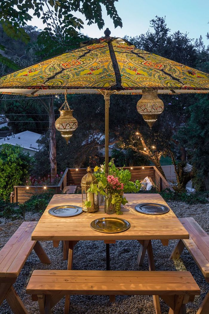colorful umbrella placed above wooden table with benches landscape lighting ideas lanterns hanging from it