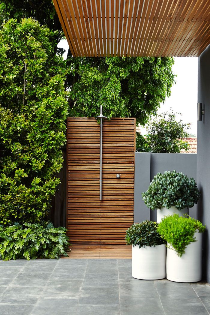 contemporary architecture outside showers wood wall with shower head surrounded by plants and trees