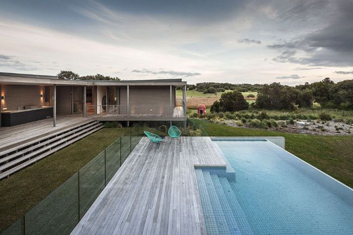 contemporary house with infinity pool garden furniture next to it pool landscaping ideas