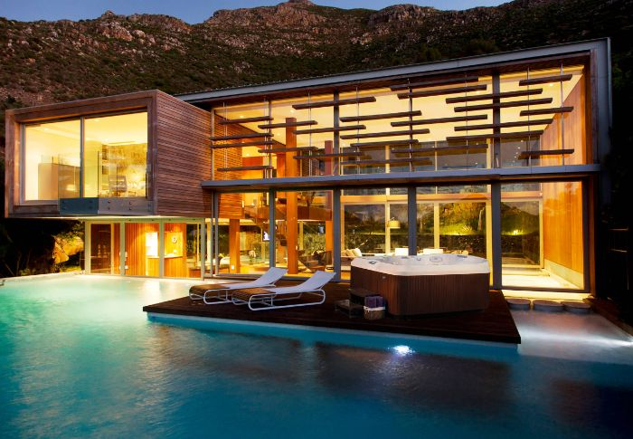 contemporary house with large pool small inground pool cost deck with lounge chairs and jacuzzi