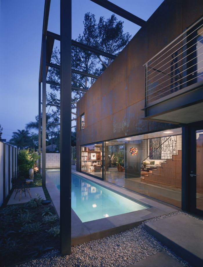 contemporary house with small inground pools small flower bed on the side gravel on the other
