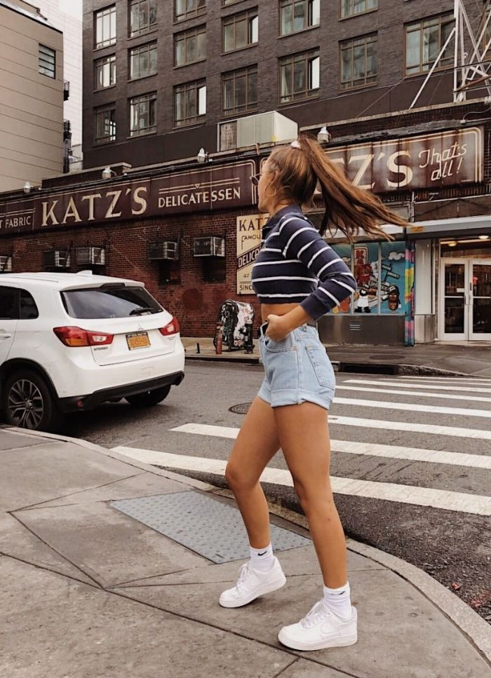 dark blue and white striped cropped blouse denim shorts white sneakers cute clothes for teenage girl worn by brunette girl