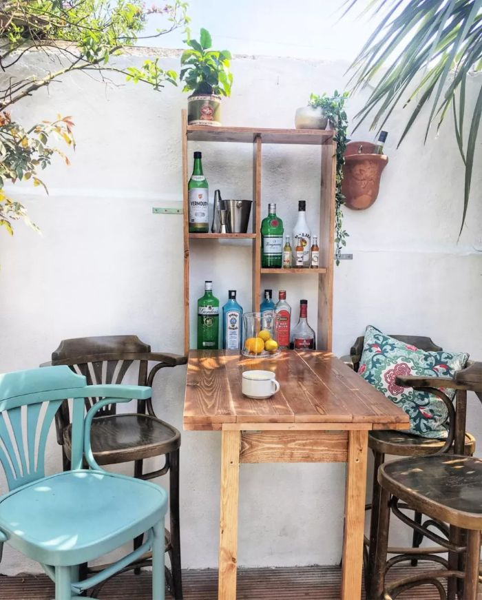 different chairs around small bar outdoor patio bar four shelves with bottles and potted plants