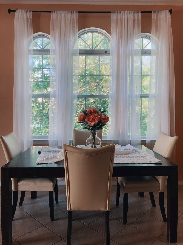 dining room with three tall windows window installation square black wooden table four white leather chairs