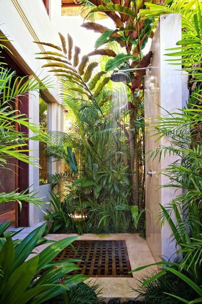 diy outdoor shower enclosure shower mounted on white wall surrounded by plants bushes and trees