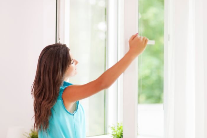 door installation woman with long brown hair wearing blue top opening window