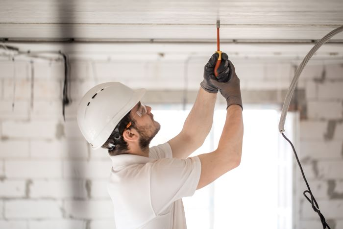 electrician installer with tool in his hands home remodeling working with cable on construction site