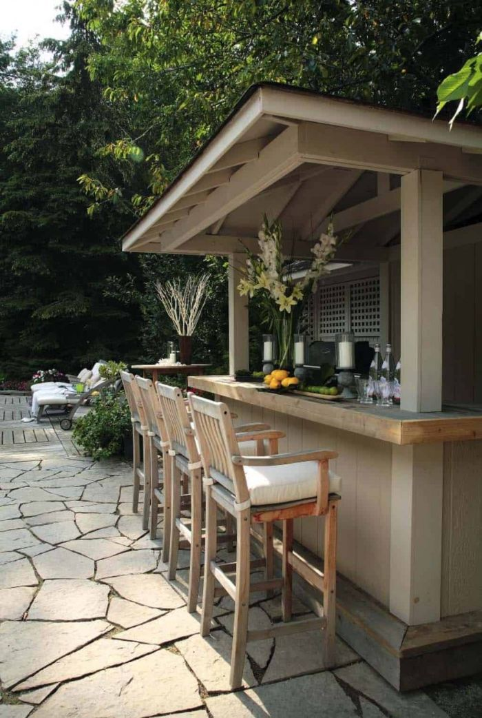 enclosed mini bar with four wooden bar stools outdoor kitchen bar glasses bottles limes lemons on top