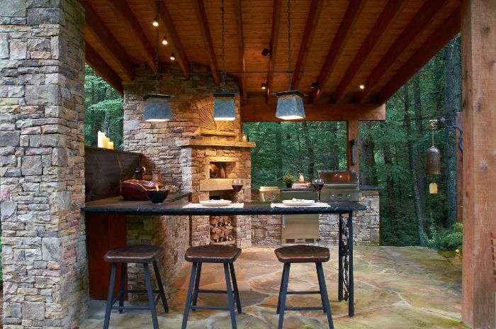 enclosure made with stones with fireplace and barbecue backyard bar ideas three bar stools next to bar with black countertop