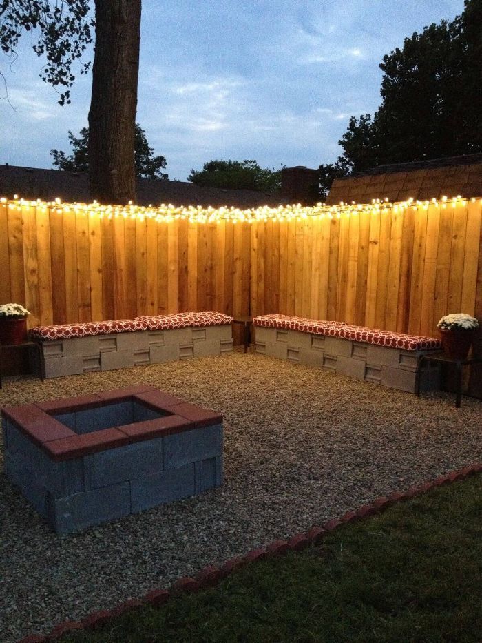 fairy lights hanging on top of wooden fence backyard lighting ideas garden benches and fire pit